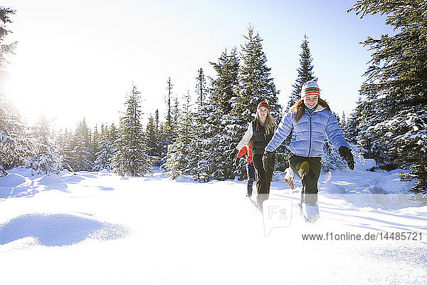 Three young women on snowshoes enjoy the outdoors near Homer  Alaska during winter.
