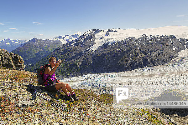 Female hiker taking a break and talking on a cell phone next to Exit Glacier in the Harding Icefield near Seward  Kenai Fjords National Park  Kenai Peninsula  Southcentral Alaska  Summer  HDR