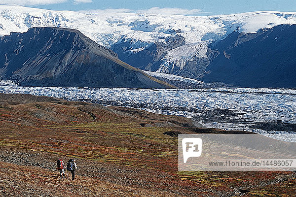 Pair of backpackers hike through the fall landscape toward Long Glacier at Wrangell-St.Elias National Park in Southcentral Alaska.