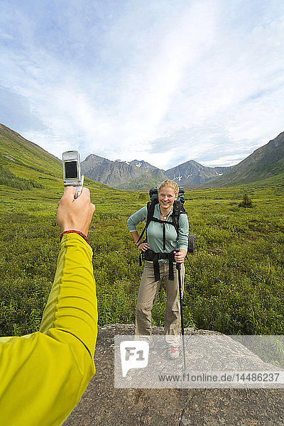 Hiker uses cell phone to take picture of friend along South Fork Eagle River trail in Chugach State Park Alaska Summer