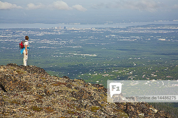 Woman hiker takes in view of Anchorage  Alaska on McHugh Peak trail in Chugach State Park