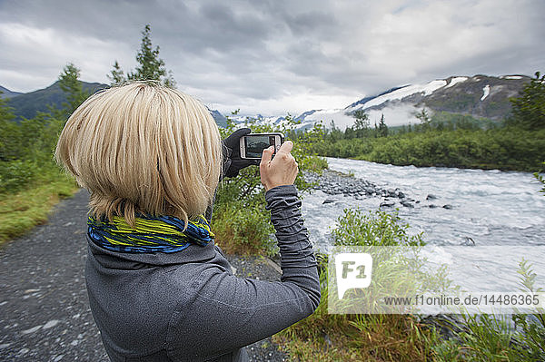Woman using a smartphone to photograph Portage Creek  Portage Valley  Southcentral Alaska