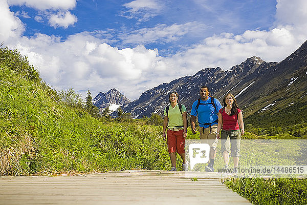 Family hiking on the boardwalk of the Middle Fork Loop Trail in the Glen Alps area of Chugach State Park  southcentral Alaska