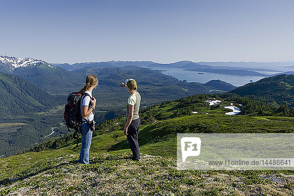 Hikers pause to admire the view in the alpine above Amalga Basin in the Tongass Forest  near Juneau  Alaska.