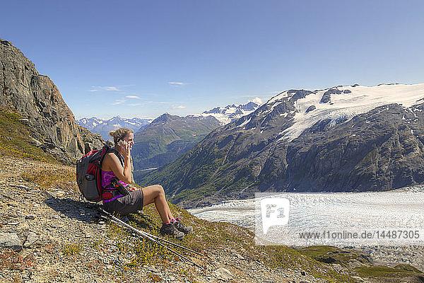Female hiker taking a break and talking on a cell phone next to Exit Glacier in the Harding Icefield near Seward  Kenai Fjords National Park  Kenai Peninsula  Southcentral Alaska  Summer  HDR