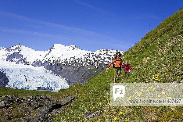 Mother & daughter hiking on steep wildflower covered mountain slope Portage Pass Trail Chugach NF Alaska
