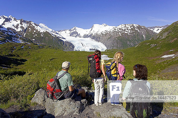 Family sitting on rock viewing Portage Glacier from Portage Pass Trail Chugach Mtns Alaska Summer