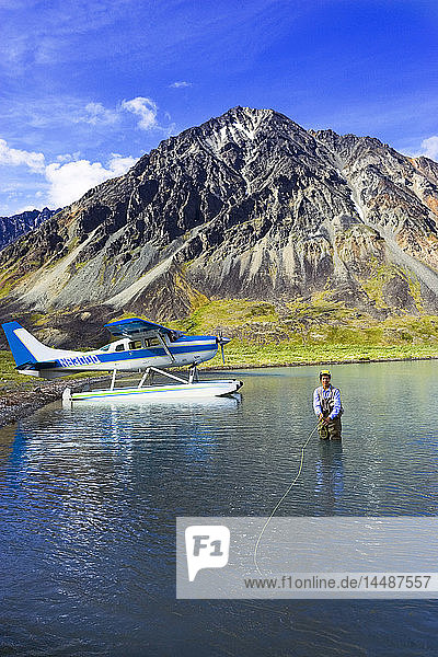 Woman flyfishing on Turquoise Lake near Cessna floatplane Lake Clark Nat Park Southcentral AK Summer