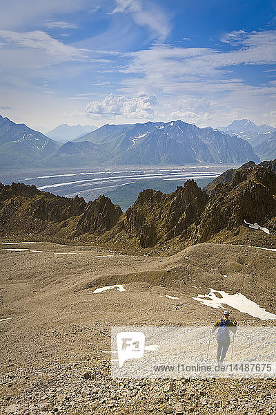 Man hiking on a rock glacier on the trail to the Jumbo Mine above Kennecott in Wrangell-St.Elias National Park  Alaska
