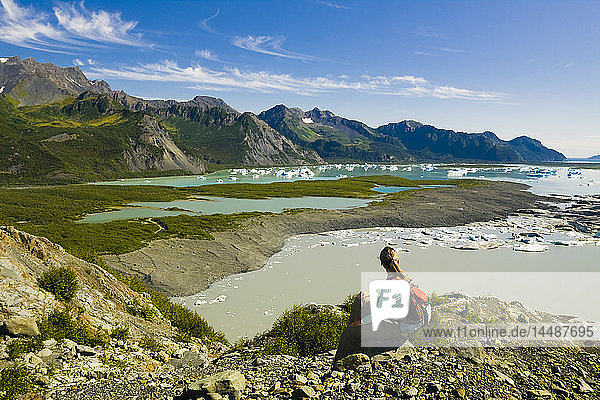 Female hiker overlooks Bear Glacier Lake in Kenai Fjords National Park  Kenai Peninsula  Southcentral Alaska  Summer