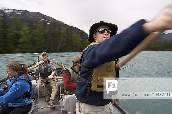 Couple spinfishing from drift boat on Kenai River Kenai Peninsula Alaska Summer Blurred Action