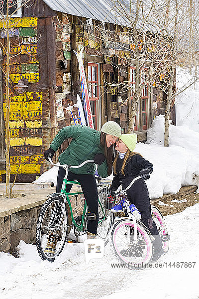Mother and daughter ride their bikes in Winter on the streets of Crested Butte  Colorado