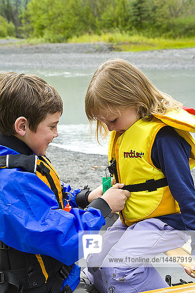 Young boy helps younger sister buckle up a life vest before canoeing on Eagle River in Chugach State Park during Summer in Southcentral Alaska