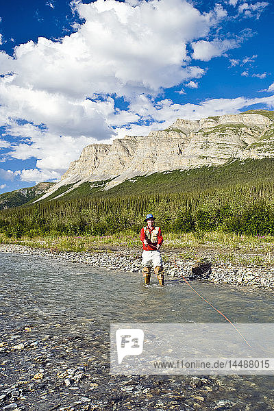 Man fly fishing on the Dietrich River in the Brooks Range during Summer in Alaska