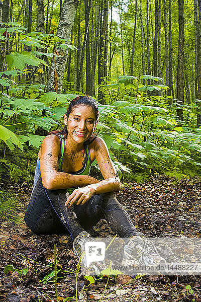 Young Hispanic woman resting after run on muddy trail  Southcentral Alaska