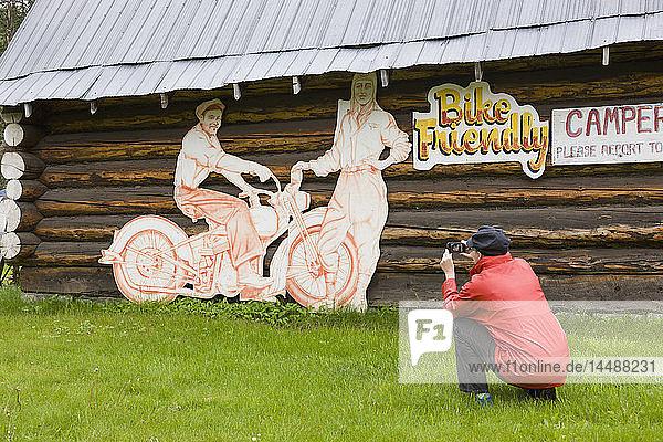 Woman tourist photographs a log cabin and motorcycle sign at the Tetsa River Lodge  British Columbia  Canada  Summer