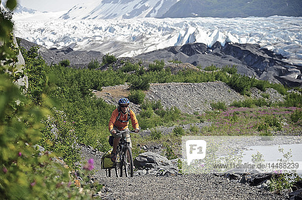 Woman bicycling on the trail to Spencer Glacier  Chugach National Forest  Kenai Peninsula  Southcentral Alaska  Summer
