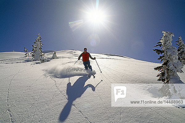 Man downhill skiing Southeast AK at ski resort Juneau Coast Mtns Winter