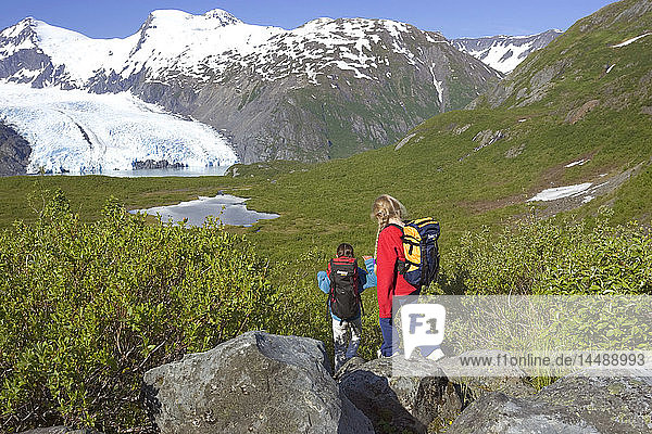 personFamily hiking together on Portage Pass Trail w/Portage Glacier Chugach Mtns & Nat Forest Alaska