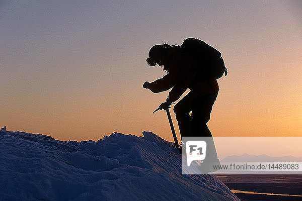 Person ice climbing sunset Chugach Mtns Southcentral Alaska winter silhouette