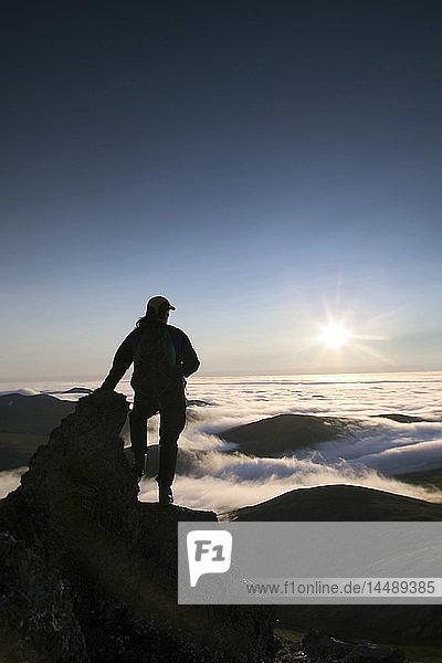 Hiker on Rock Views Cloud Layer Caribou Pass AK ANWR AR Brooks Range Silhouette