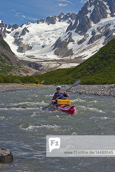 Female kayaker maneuvers down a stream in the Northwestern Fjord of Kenai Fjords National Park  Kenai Peninsula  Southcentral Alaska  Summer
