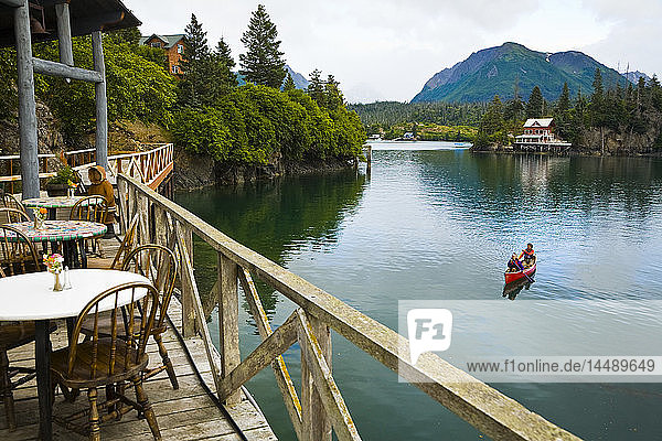 Two women in tandem canoe leave the The Saltry Restaurant on the waterfront in Halibut Cove in Kachemak Bay  Southcentral  Alaska