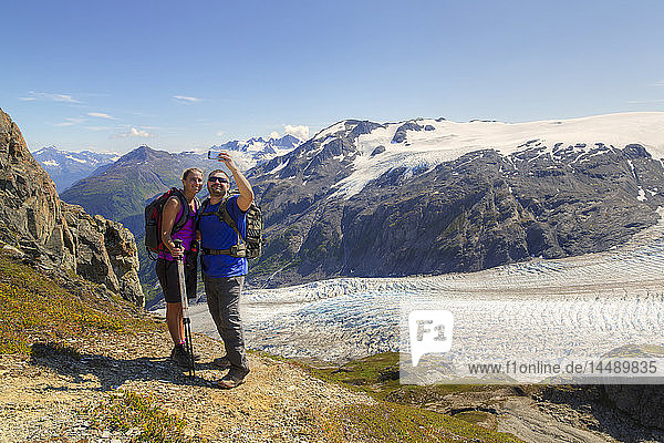 Hikers take a selfie with a smart phone from the Harding Icefield Trail near Seward  Kenai Fjords National Park  Kenai Peninsula  Southcentral Alaska  HDR