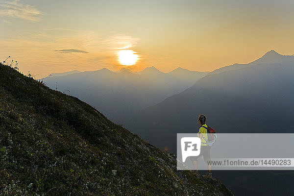 Hiker on the steep hillside of Mt. Alyeska watching the sun set over Girdwood Valley in Southcentral Alaska