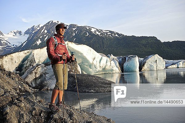 Female hiker at Spencer Glacier with the Chugach Mountains in the background  Chugach National Forest  Kenai Peninsula  Southcentral Alaska  Summer