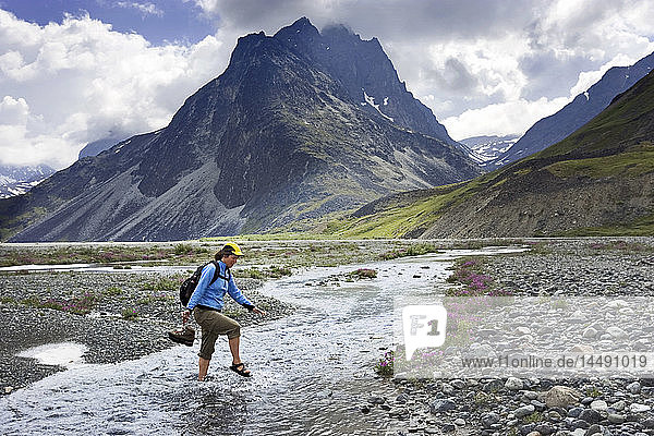 Female hiker wading across stream in sandals Lake Clark National Park near Turquoise Lake AK Summer