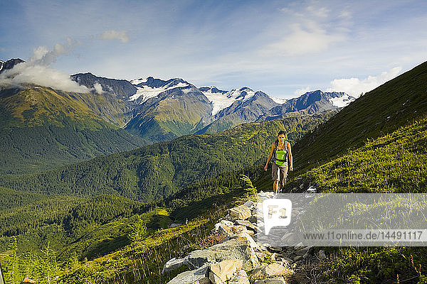 Young adult Hispanic woman hiking to the top of the tram on Mt. Alyeska above Girdwood in Southcentral Alaska