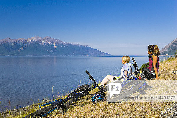 Bicyclists rest after riding on Coastal Trail overlooking Turnagain Arm and Kenai Mountains near Bird Creek in Southcentral Alaska