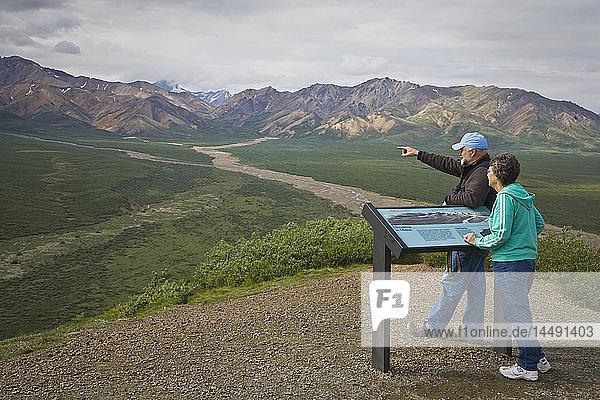 Mature couple overlooks valley from Polychrome pass overlook interpretive sign in Denali National Park  Alaska during Summer