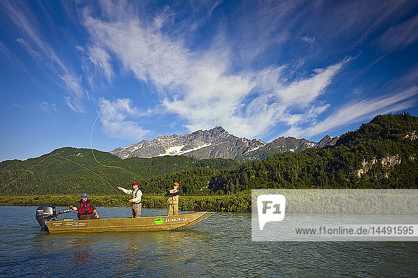 Man and woman fly fishing for salmon from boat on Big River Lakes with fishing guide with the Chigmit Mountains in the background during Summer Southcentral Alaska