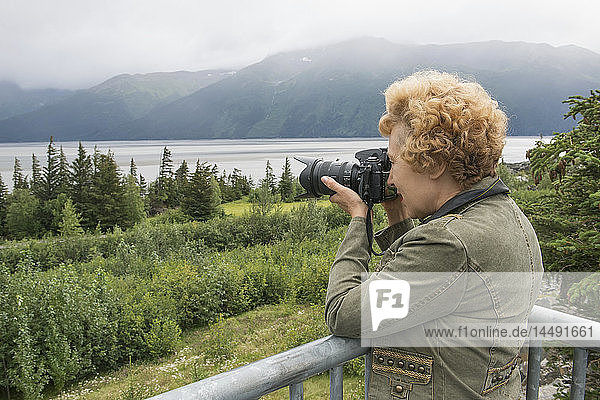 Senior woman photographing Turnagain Arm on a cloudy day  Southcentral Alaska