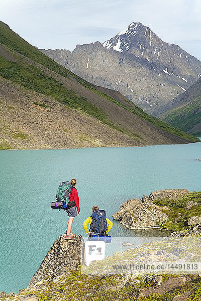 Male & female hikers on South Fork Eagle River Trail next to Eagle Lake in Chugach State Park Alaska Summer