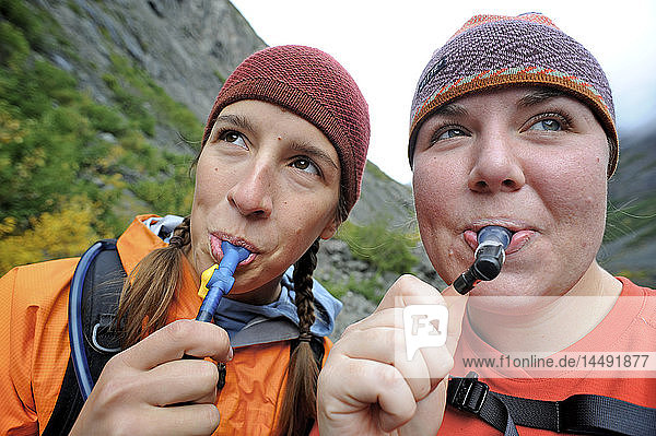 Female hikers take a water break while hiking along the Eklutna River in Chugach State Park  Southcentral Alaska