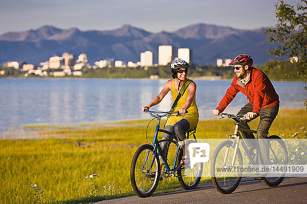 Bicyclists riding on the Tony Knowles Coastal Trail with the Anchorage skyline in the background  Southcentral Alaska