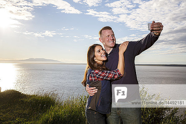 Young couple using a smart photo to take a selfie at sunset  Point Woronzof  Anchorage  Southcentral Alaska  Summer