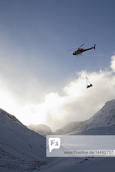 Helicopter carrying sledge near snowcapped mountain