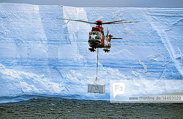 Helicopter carrying carton near glacier