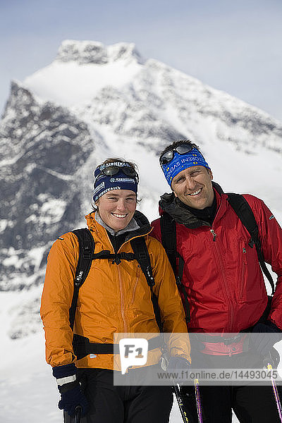 Two people standing near snowcapped mountain