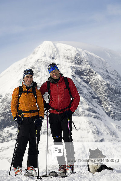 Two people standing with dog near snowcapped mountain