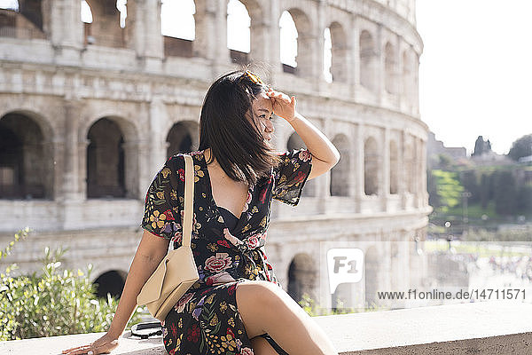 Young woman sitting in front of Coliseum  Rome  Italy