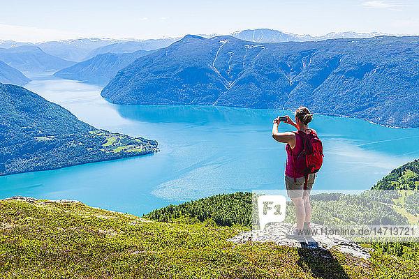 Woman taking photo of lake