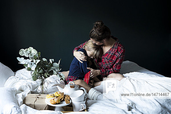Mother with daughter on bed