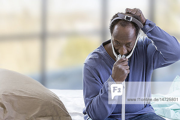 Man using a CPAP (Continuous Positive Airway Pressure) mask to treat sleep apnea syndrome.