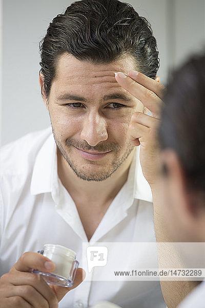 Man applying face cream.