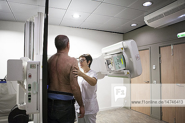 Reportage in a radiology centre in Haute-Savoie  France. A technician positions a patient for a collarbone x-ray.